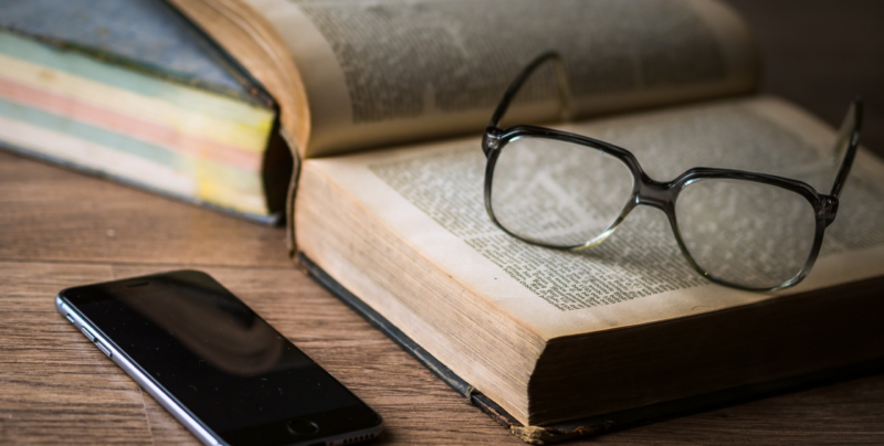 Open book, glasses, and phone